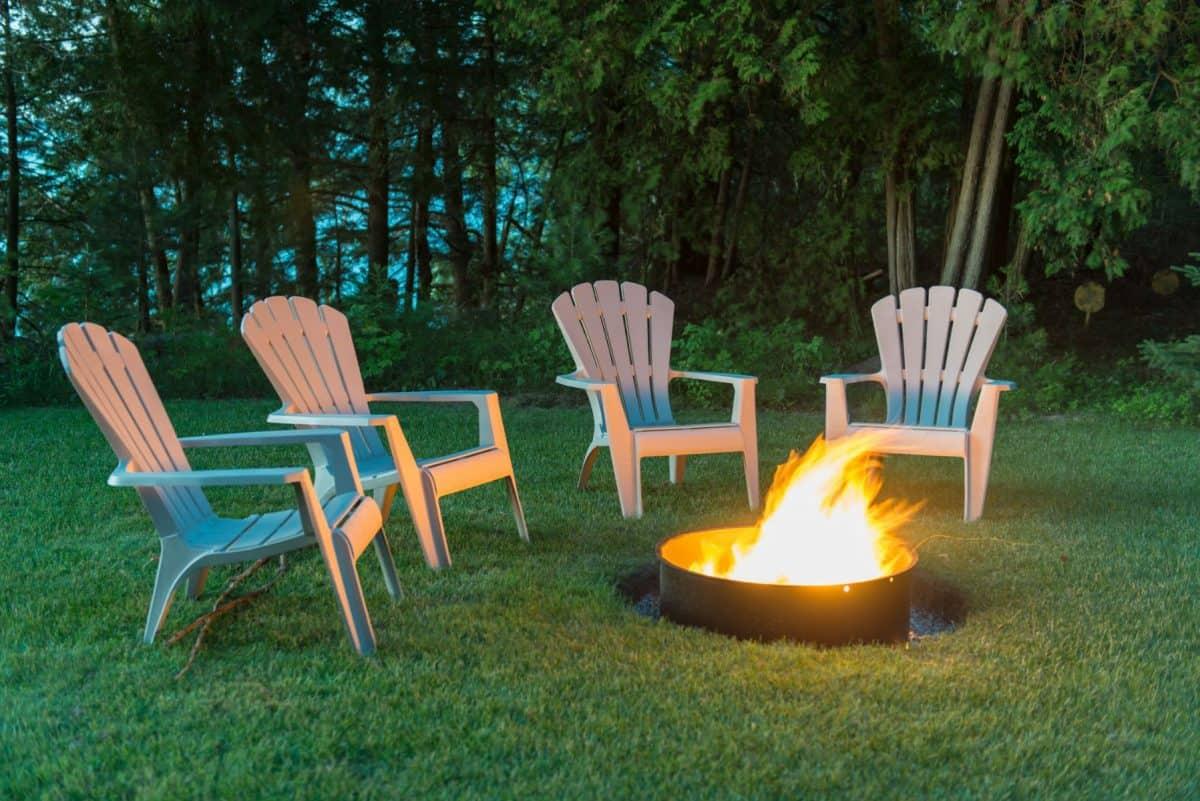 4 Muskoka chairs around a camp fire.