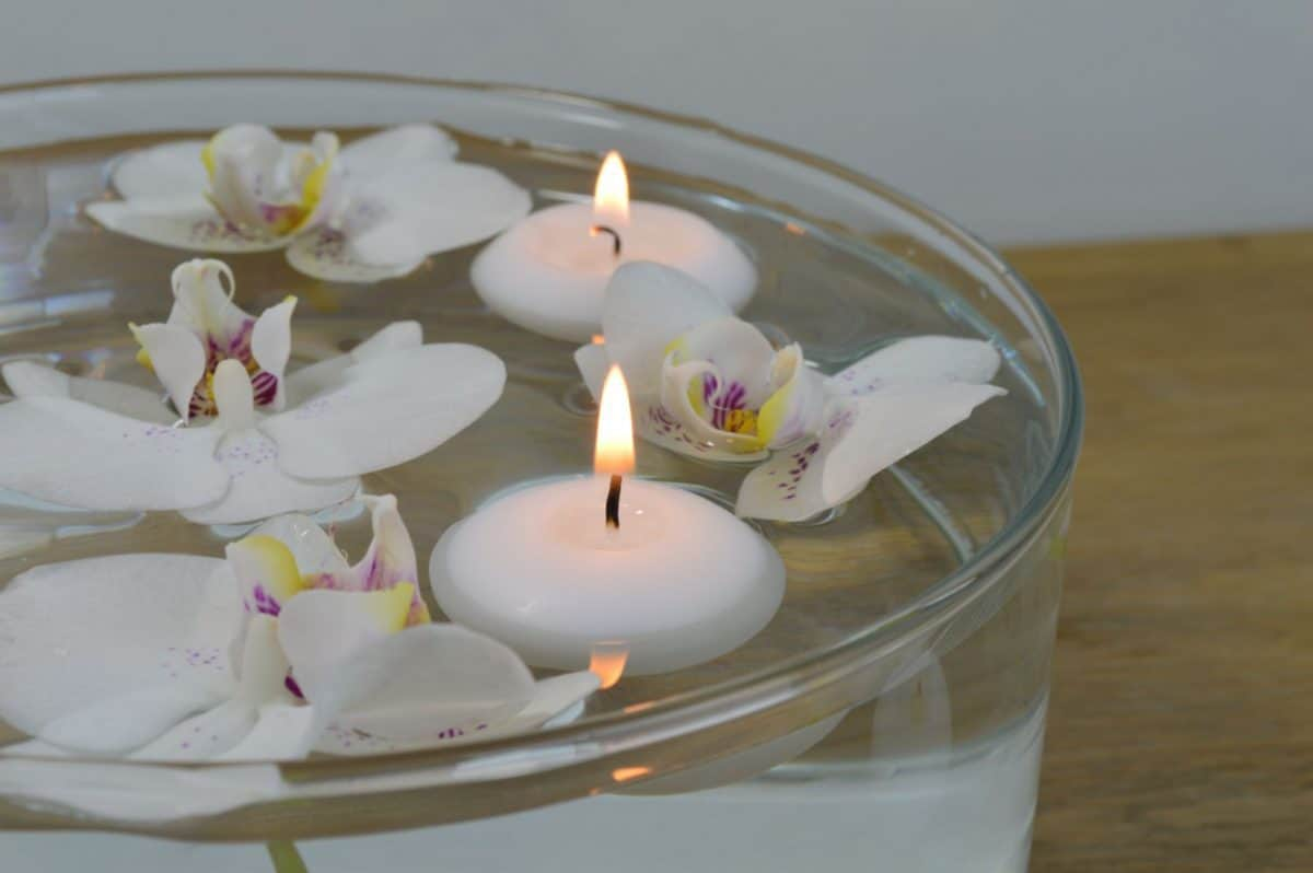 White and purple orchids with candles floating in a bowl of water