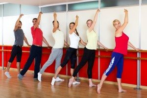 Happy people rehearsing ballet dance in studio