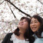 happy sisters under cherry blossom tree