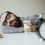 Man with beard in glasses sleeps in office on the table over laptop with coffee in hand