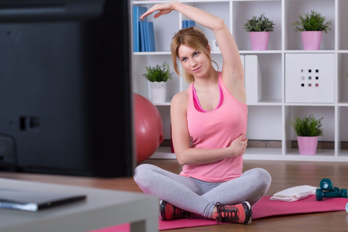 Young woman is training in front of television