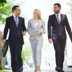 Vertical image of a business team walking in step in the city