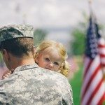 American soldier who is wearing an American military uniform is holding his daughter in a field of flags