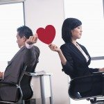 Work romance between two business people holding a heart