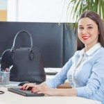Portrait of attractive young businesswoman sitting at her desk in an office typing on computer keyboard