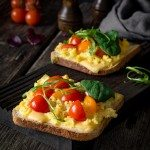 Breakfast toast with scrambled eggs, cheese, cherry tomatoes, arugula and corn salad on rustic wooden background