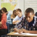 Teenage African American male wearing a plaid button-up shirt sitting at a desk in class. He is writing in a notebook on his desk using a pencil.  Around him are his classmates, also writing on their papers.  They are all concentrating on their own work.