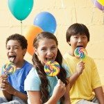 Multiracial children at a party with lollipop and balloons.  Focus on girl, 11 years.