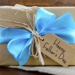 Happy Fathers Day natural kraft paper wrapped gift owith pale blue ribbon on dark wood background.