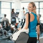Fit woman holding gym bag in a fitness centre. Beautiful blonde woman ready to start her training. Portrait of energetic woman looking at camera ready for new inscription at the gym.
