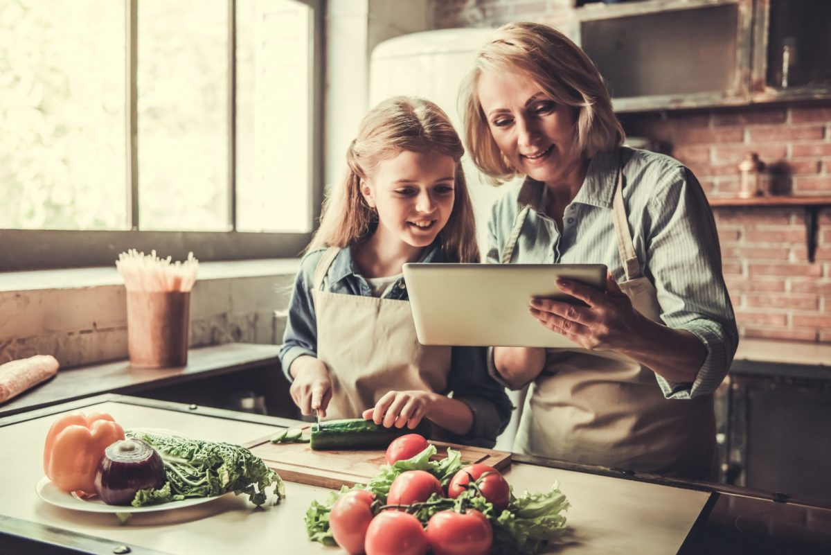 Beautiful grandma and granddaughter are using a digital tablet and smiling while preparing salad in kitchen