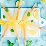 Lemonade popsicles with lemon slices, fresh mint leaves and ice cubes on white ceramic board over blue turquoise tray, top view
