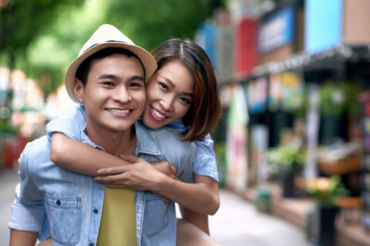 Portrait of hugging Asian couple standing outdoors