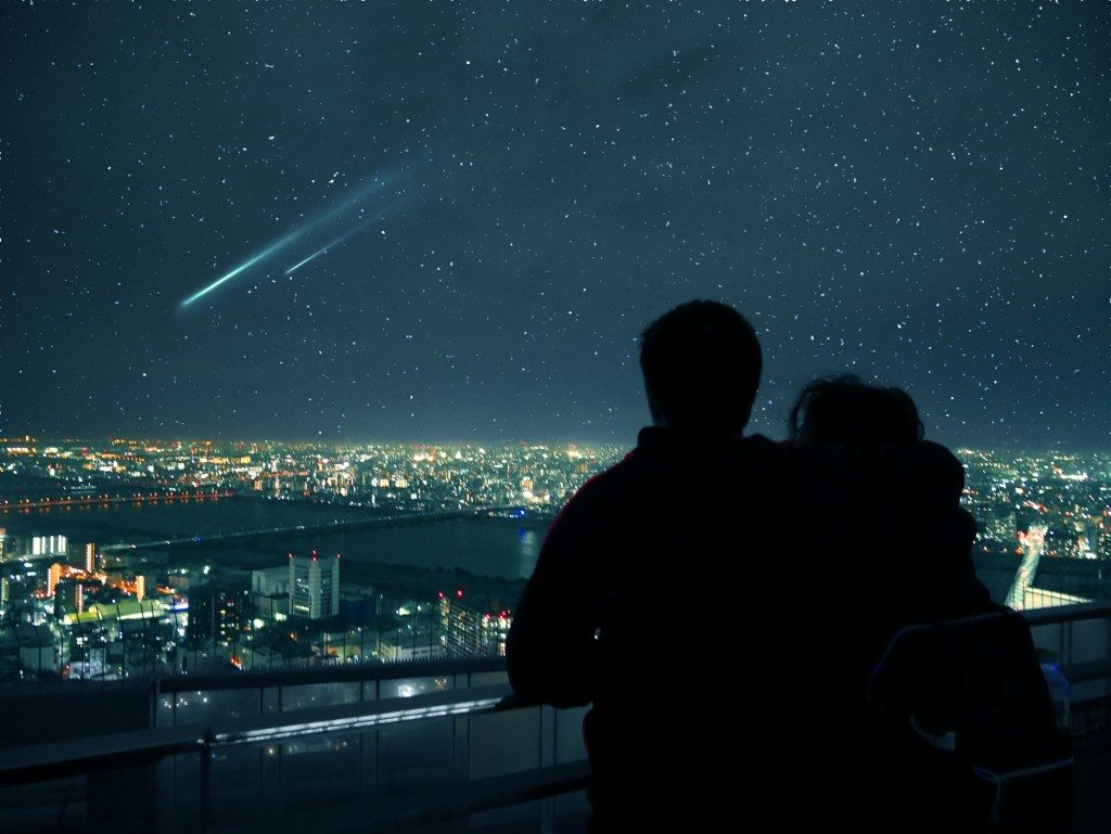 Couple looking over Osaka night skyline and falling stars
