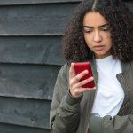 Outdoor portrait of beautiful sad depressed mixed race African American girl teenager female young woman texting on red cell phone wearing green bomber jacket