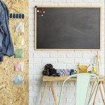 Interior with brick wall, blackboard, desk, chair and OSB board