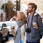 tourist couple travel with coffee ab camera walk through city having fun