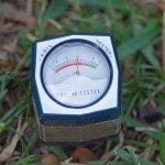 pH Soil Testin meter reading 6 on the scale as it is inserted into a Florida lawn.