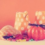 Retro Happy Halloween trick or treat candy in orange polka dot party favor bags with vintage style filter.