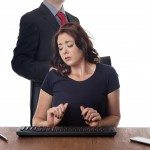 business woman sitting at her desk with a male work colleague touching her on the shoulder